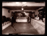 Men in a cigar store with pool hall and shoeshine stand